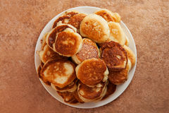Pila di pancake fritti su un piatto bianco Fotografie Stock