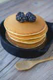 Pila di pancake in padella con le more e lo syru dell'acero Fotografie Stock Libere da Diritti