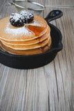 Pila di pancake in padella con le more e lo syru dell'acero Fotografia Stock