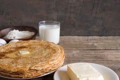 Pila di pancake russi o ucraini tradizionali con burro e gli ingredienti sulla tavola di legno rustica Fotografie Stock Libere da Diritti