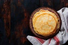 Pila di pancake sottili casalinghi con i pezzi di burro, di latte e di miele sul vecchio piatto ceramico rustico fotografia stock libera da diritti