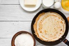 Pila di pancake sulla padella con gli ingredienti sulla tavola bianca Fotografia Stock Libera da Diritti
