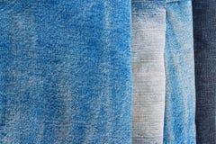 Pila di pantaloni delle blue jeans come priorità bassa Fotografia Stock