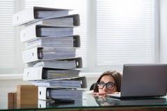 Pila di Peering The Folders della donna di affari in ufficio fotografie stock