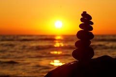Pila di pietre differenti nell'equilibrio al tramonto della spiaggia fotografia stock