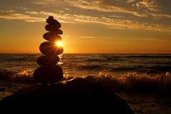Pila di pietre differenti nell'equilibrio al tramonto della spiaggia immagini stock libere da diritti