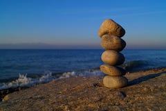 Pila di pietre differenti nell'equilibrio alla spiaggia fotografia stock
