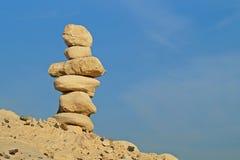Pila di pietre differenti nell'equilibrio con le mani del bambino fotografia stock