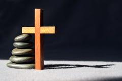 Pila di pietre liscie con un incrocio di legno semplice Immagini Stock Libere da Diritti