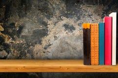 Pila di pila di vecchi libri di libri variopinti e di libro elettronico sugli scaffali di legno Immagine Stock Libera da Diritti