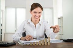 Pila di Placing Coin To della donna di affari di monete fotografie stock libere da diritti