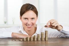 Pila di Placing Coin To della donna di affari di monete fotografia stock