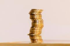 Pila di primo piano delle monete su un fondo dell'oro Fotografia Stock