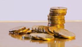 Pila di primo piano delle monete su un fondo dell'oro Fotografia Stock Libera da Diritti