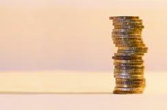 Pila di primo piano delle monete su un fondo dell'oro Immagini Stock Libere da Diritti