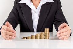 Pila di Putting Coin On della donna di affari di monete dorate fotografia stock libera da diritti