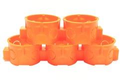 Pila di scatole elettriche arancio su fondo bianco Immagini Stock