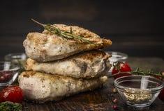 Pila di seno di pollo arrosto con condimento fritto e di pomodori su fondo di legno scuro fotografia stock
