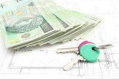 Pila di soldi con la chiave che si trova sul piano dell'alloggio Fotografie Stock