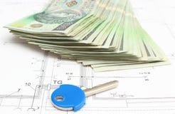 Pila di soldi con la chiave che si trova sul piano dell'alloggio Fotografia Stock