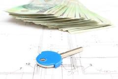 Pila di soldi con la chiave che si trova sul piano dell'alloggio Immagine Stock Libera da Diritti