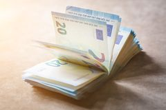 Pila di soldi degno 20 bugie degli euro su una superficie marrone chiaro del tessuto nei raggi del sole Fotografie Stock Libere da Diritti