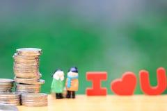 Pila di soldi delle monete e di condizione miniatura delle coppie sul fondo verde naturale, risparmiando per l'amante o la famigl immagine stock libera da diritti