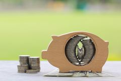 Pila di soldi delle monete in legno del porcellino salvadanaio sul backgro verde naturale immagini stock