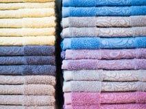 Pila di spugne variopinte piegate Casa del negozio Numerosi asciugamani impilati e piegati sugli scaffali di un deposito Fotografia Stock