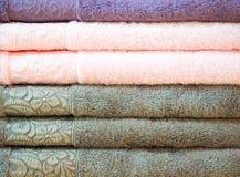 Pila di spugne variopinte piegate Casa del negozio Numerosi asciugamani impilati e piegati sugli scaffali di un deposito Fotografia Stock Libera da Diritti