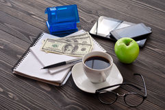 Pila di taccuino con una tazza di caffè, soldi, casa fotografie stock