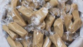 Pila di taffy del caramello, popolare, confetteria della colata-in-vostro-bocca, avvolta in cellofan trasparente, in un negozio d Immagine Stock Libera da Diritti