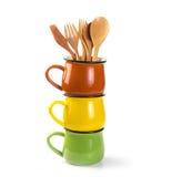 Pila di tazze variopinte della minestra con il cucchiaio di legno e la forchetta isolati Fotografia Stock