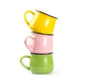 Pila di tazze variopinte della minestra su fondo bianco Fotografia Stock