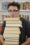 Pila di trasporto dell'allievo di libri in libreria Fotografie Stock Libere da Diritti