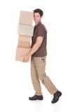 Pila di trasporto dell'uomo di scatole Fotografia Stock Libera da Diritti