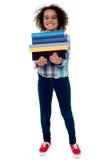 Pila di trasporto della bambina sveglia di libri Fotografie Stock