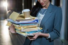 Pila di trasporto della donna di affari di cartelle di archivio mentre per mezzo del telefono cellulare Immagine Stock Libera da Diritti