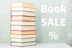 pila di vecchi libri colorati sullo scaffale e sul fondo verde con testo & x22; Vendita di libro %& x22; fotografia stock