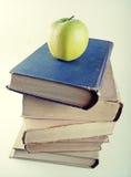 Pila di vecchi libri dalla copertina rigida con la mela verde Fotografia Stock Libera da Diritti