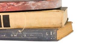 Pila di vecchi libri isolati sui precedenti bianchi Immagini Stock