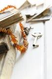 Pila di vecchie fotografie con la collana ambrata sull'album di foto su fondo bianco Immagine Stock Libera da Diritti