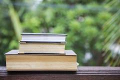 Pila di vecchio libro sulla tavola di legno sopra il fondo verde naturale vago del giardino Fotografia Stock