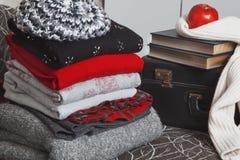 Pila di vestiti e di libri di inverno con il bordo lucido Immagine Stock