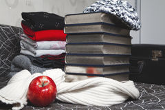 Pila di vestiti e di libri di inverno con il bordo lucido Immagini Stock Libere da Diritti