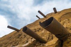 Pila enorme de basura de mina y de tubos oxidados del metal Imagenes de archivo