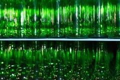 Pila enorme de botellas de cristal vacías en la tabla azul Fotos de archivo libres de regalías