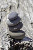 Pila equilibrata di pietre grige su legname galleggiante fotografia stock