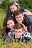 Pila feliz: grupo de gente joven y de campo verde Imagenes de archivo