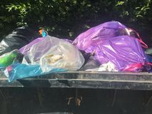 Pila grande de basura en envases contra un cielo azul fotografía de archivo